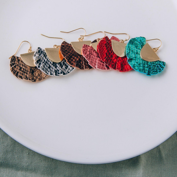"Feather inspired tassel earrings featuring snakeskin print and a gold metal accent. Approximately 1"" in length."
