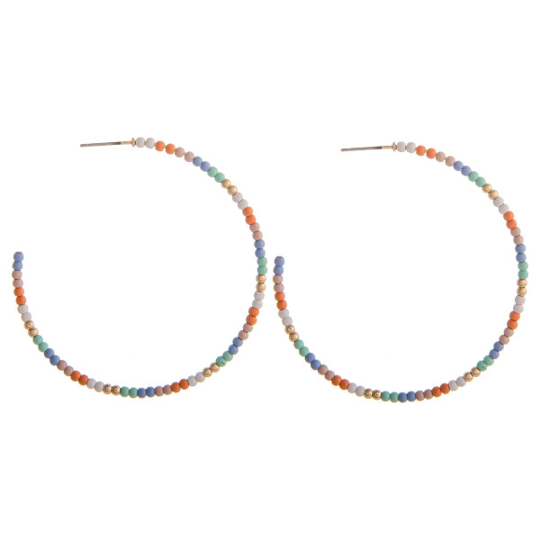 "Large multicolored beaded hoop earrings featuring gold accents. Approximately 2.5"" in diameter."