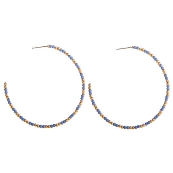 "Large light blue beaded hoop earrings featuring gold accents. Measures approximately 2.5"" in diameter."