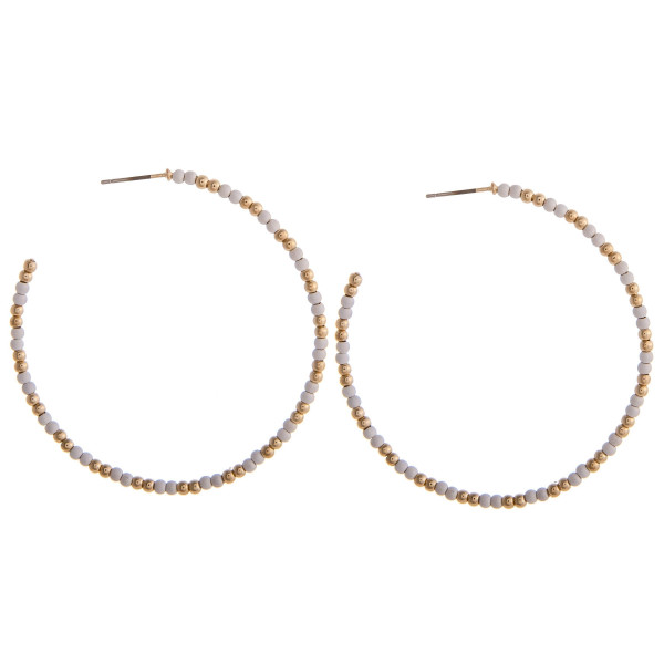 "Large white beaded hoop earrings featuring gold accents. Measures approximately 2.5"" in diameter."