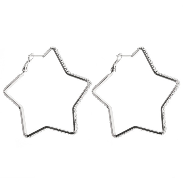 "Silver star hoop earrings featuring cubic zirconia detailing. Approximately 2"" in diameter."