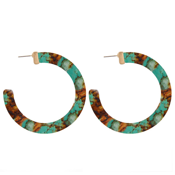 "Wood hoop earrings featuring a brown and turquoise inspired pattern. Measure approximately 2.5"" in diameter."