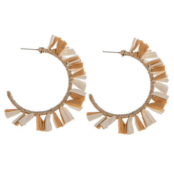 "Large hoop earrings featuring beige and ivory tassel accents. Approximately 2"" in diameter."