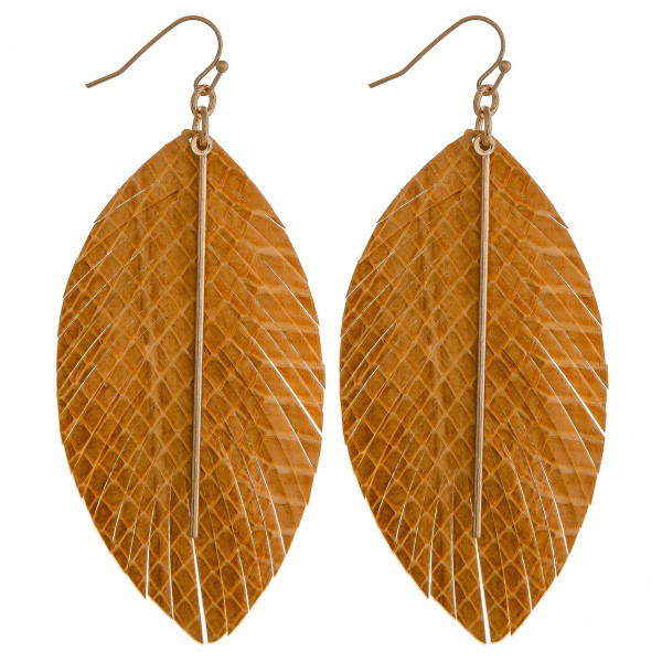 "Faux leather snakeskin feather dangle earrings featuring a gold bar accent. Approximately 3.5"" in length."