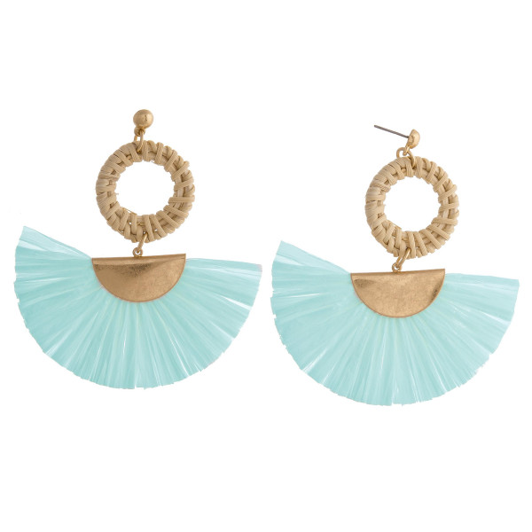 """Raffia tassel earrings featuring a rattan woven circular accent with a stud post. Approximately 3"""" in length."""