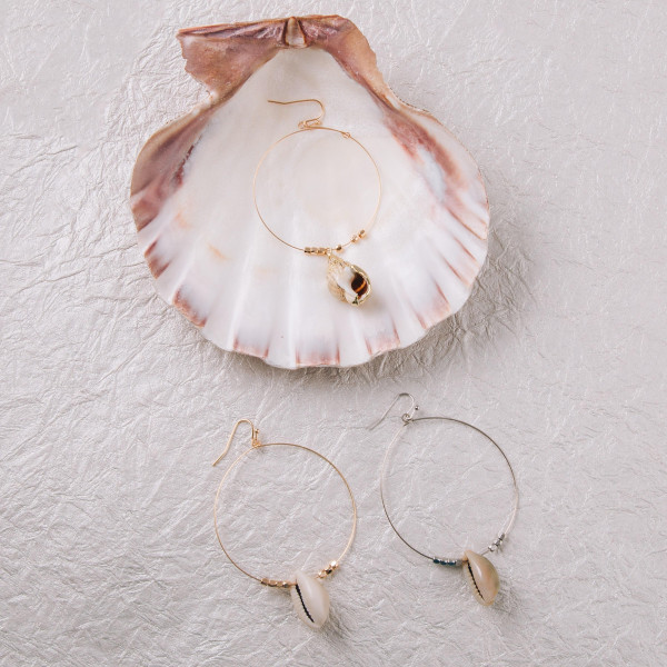 "Dainty circular earrings featuring a seashell detail and beaded accents. Approximately 2"" in diameter. Seashell approximately 1"". Approximately 3"" in length overall."