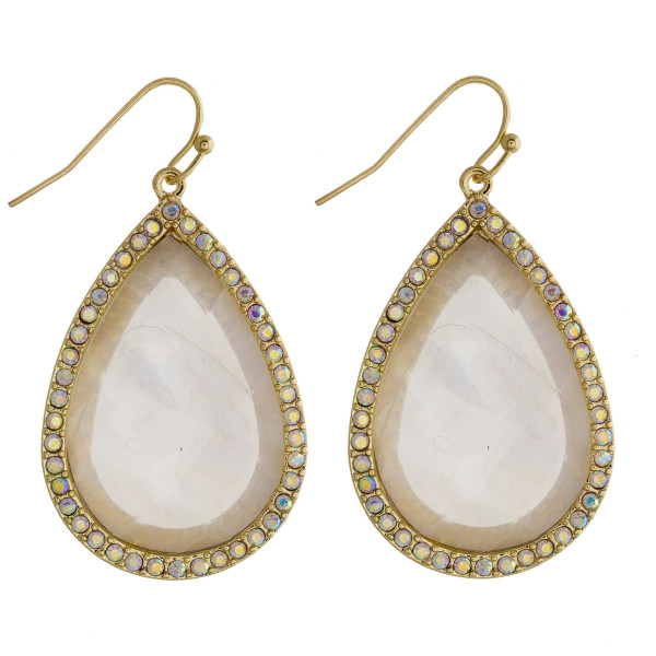 "Gold teardrop earrings featuring a white natural stone and rhinestone details. Approximately 1.5"" in length."
