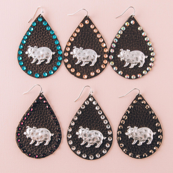 """Faux leather teardrop earrings featuring a metal pig detail and brown rhinestone accents. Approximately 2.5"""" in length."""