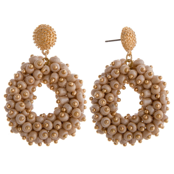 """Long beige circular beaded earrings with gold details. Measures approximately 1.5"""" long."""