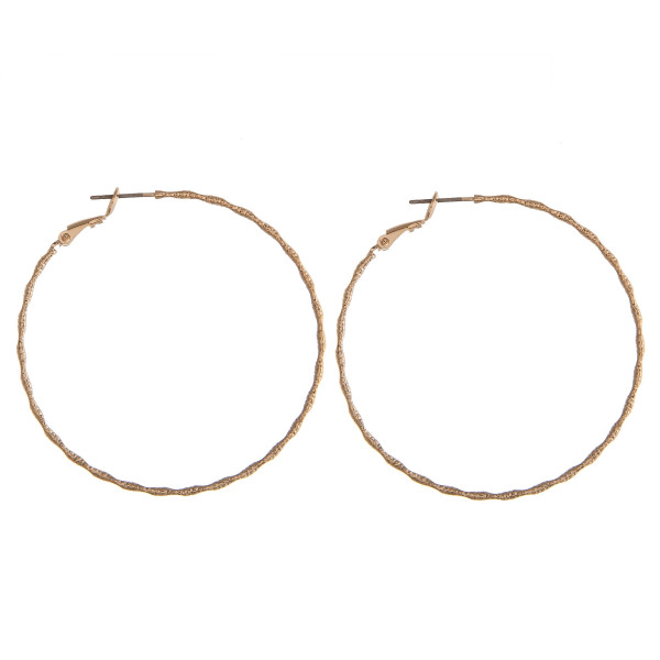 """Thin gold hoop earrings featuring a wavy, ridged texture. Approximately 2"""" in diameter."""