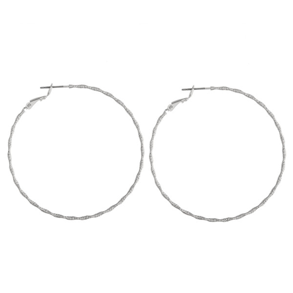"""Thin silver hoop earrings featuring a wavy, ridged texture. Approximately 2"""" in diameter."""