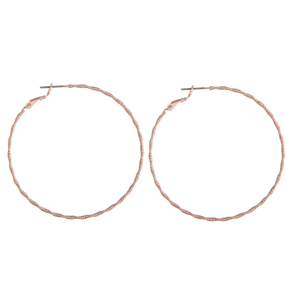 """Thin rose gold hoop earrings featuring a wavy, ridged texture. Approximately 2"""" in diameter."""