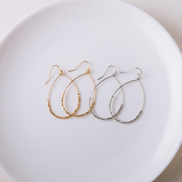 "Metal teardrop earrings featuring beaded accents. Approximately 1"" in diameter."