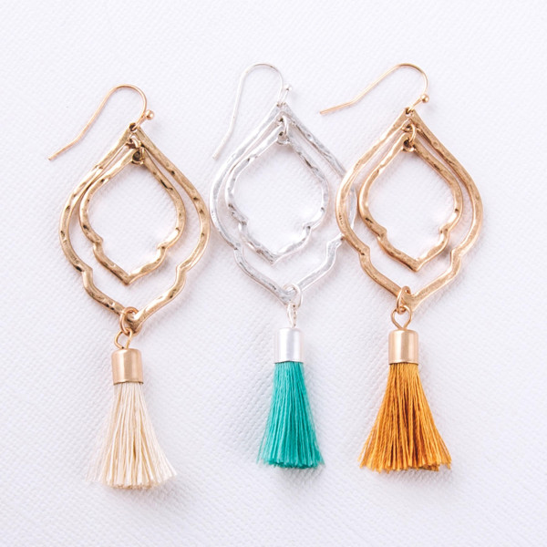 """Drop metal earrings featuring a hammered texture and ivory fanned tassel accents. Approximately 2.75"""" in length."""