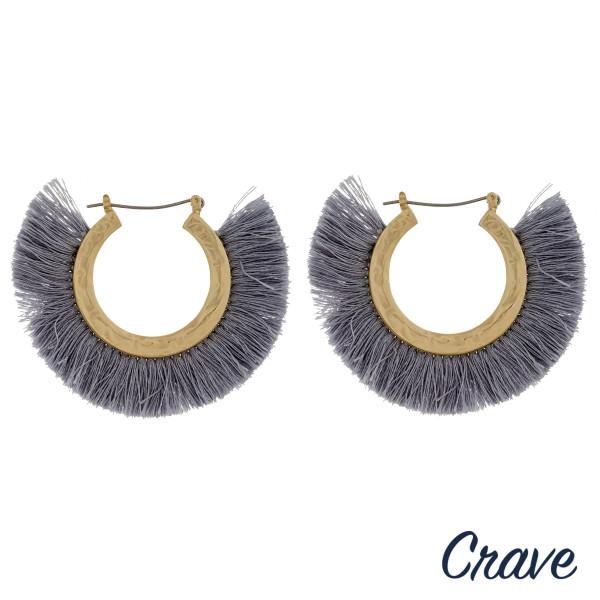 """Gold metal hoop earrings featuring grey tassel detailing. Approximately 2"""" in diameter."""