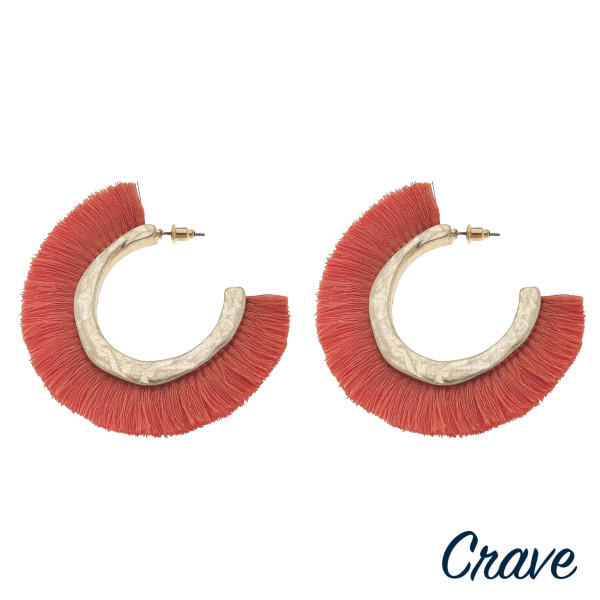 "Large hoop earrings featuring orange fabric tassel details with gold metal accents. Approximately 2.5"" in diameter."