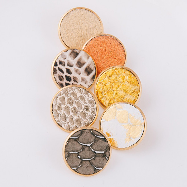 "Genuine leather stud earrings featuring a metallic snakeskin detail. Approximately 1"" in diameter."