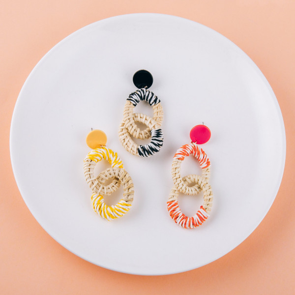 """Long rattan woven earrings featuring raffia wrapped details and a resin stud post. Approximately 3"""" in length."""