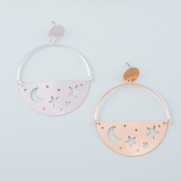 """Metal circular earrings featuring cut out moon and star accents with a stud post. Approximately 2.25"""" in length."""