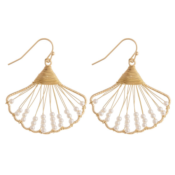 "Gold wire wrapped seashell earrings with cream beaded accents. Approximately 1"" in length."