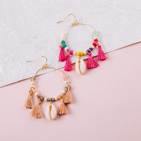 "Circular metal earrings featuring faceted beaded details with puka shell and tassel accents. Approximately 2.5"" in length."