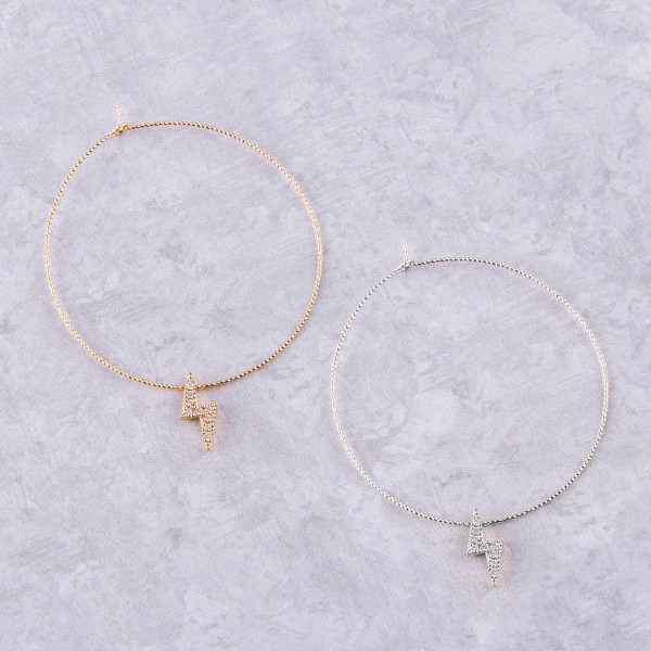 "Large dainty hoop earrings featuring a lightning bolt accent with cubic zirconia details. Approximately 2.5"" in diameter."