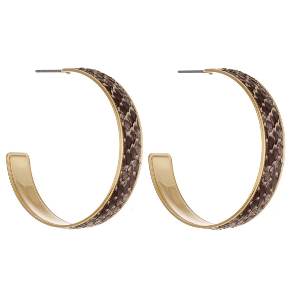 """Open hoop metal earrings featuring genuine leather snakeskin details and a stud post. Approximately 1.5"""" in diameter."""