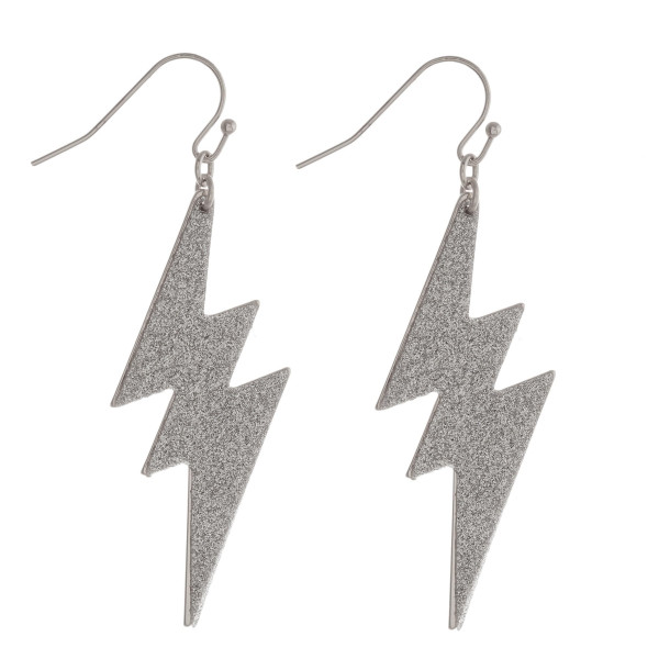 "Metal lightning bolt drop earrings featuring glitter details. Approximately 2"" in length."