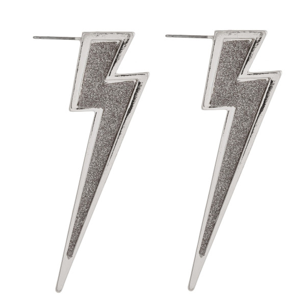 "Long metal lightning bolt earrings featuring glitter center details and a stud post. Approximately 2.5"" in length."