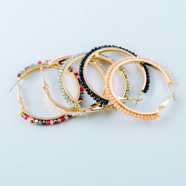 """Metal hoop earrings featuring faceted beaded details. Approximately 2"""" in diameter."""