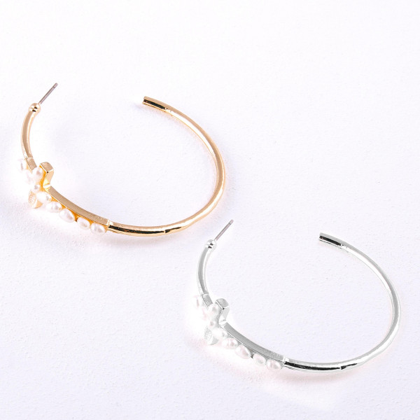 "Metal hoop earrings featuring a cross accent with pearl beaded details and a stud post. Approximately 2"" in diameter."