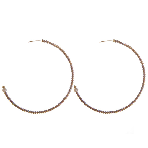 """Large hoop earrings featuring flexible wiring with iridescent beaded details and a stud post. Approximately 2.5"""" in diameter."""