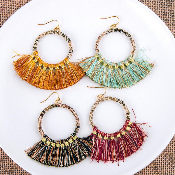 """Faux leather snakeskin wrapped round earrings with tassel accents. Approximately 3"""" in length."""