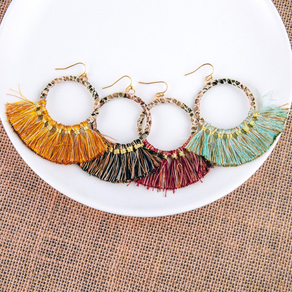 "Faux leather snakeskin wrapped round earrings with tassel accents. Approximately 3"" in length."