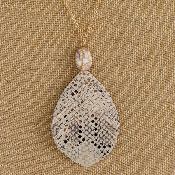 """Dainty cable chain necklace featuring a faux leather feather inspired pendant with metallic snakeskin details and a natural stone accent. Pendant approximately 3"""". Approximately 34"""" in length overall."""