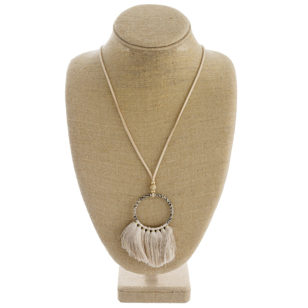 """Faux leather cord necklace featuring a circular pendant with snakeskin wrapped details and tassel accents. Pendant approximately 4"""". Approximately 38"""" in length overall."""