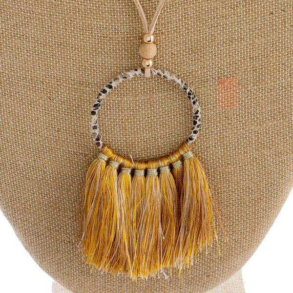 "Faux leather cord necklace featuring a circular pendant with snakeskin wrapped details and tassel accents. Pendant approximately 4"". Approximately 38"" in length overall."