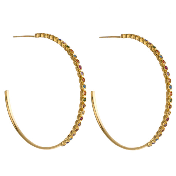 "Metal hoop earrings featuring multicolor cubic zirconia details and a stud post. Approximately 1.5"" in diameter."