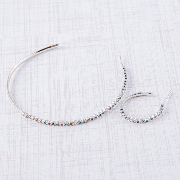 "Large dainty open hoop earrings featuring multicolor cubic zirconia details and a stud post. Approximately 2"" in diameter."