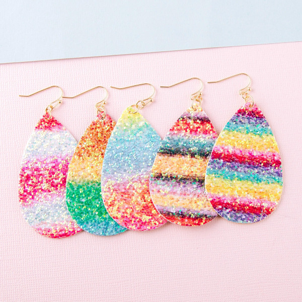"Faux leather teardrop earrings featuring rainbow details with glitter accents. Approximately 2.5"" in length."