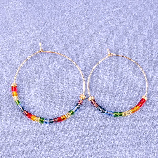 "Dainty gold hoop earrings featuring multicolor iridescent seed beaded details. Approximately 1"" in diameter."