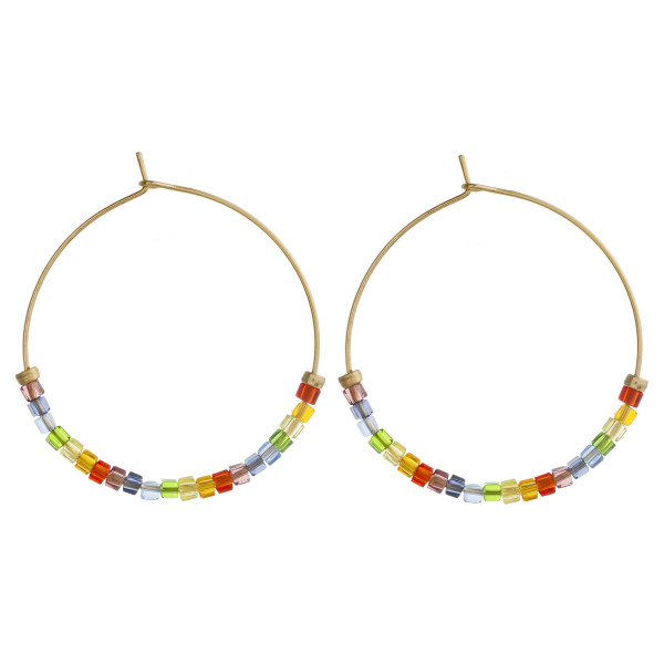 "Dainty gold hoop earrings featuring multicolor iridescent seed beaded details. Approximately 1.5"" in diameter."