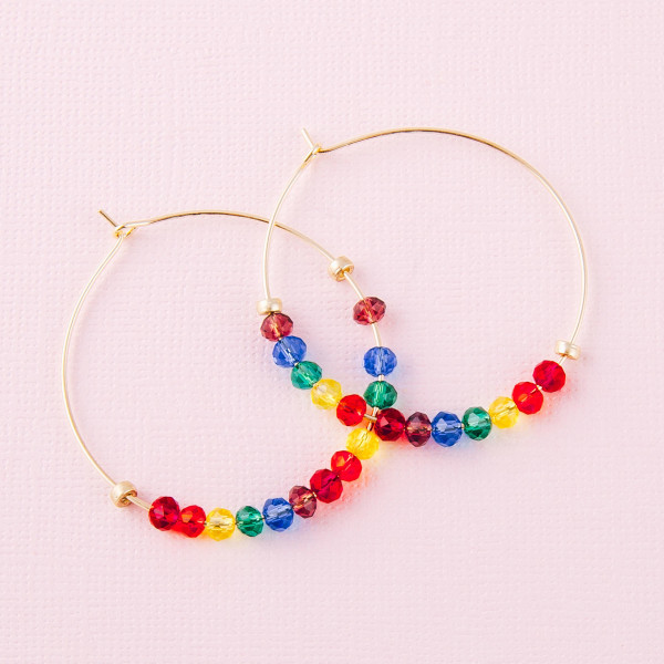 "Gold hoop earrings with multicolor faceted iridescent beaded details. Approximately 1.5"" in diameter."