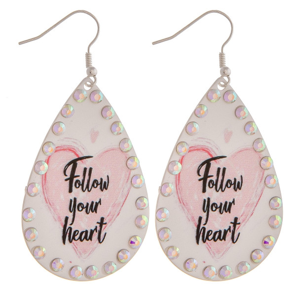 "Metal plated teardrop earrings featuring ""Follow your Heart"" inspiring message with rhinestone details. Approximately 2"" in length."