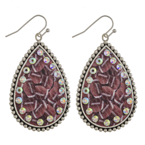 "Metal teardrop earrings featuring football faux leather details with rhinestone accents. Approximately 2"" in length."