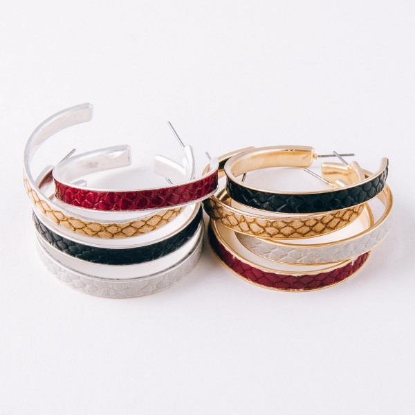 """Gold metal hoop earrings featuring faux leather snakeskin details and a stud post. Approximately 2"""" in diameter."""