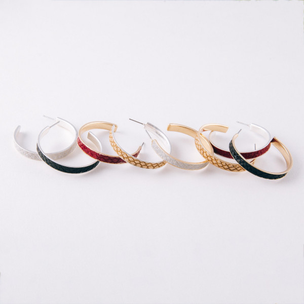 """Silver metal hoop earrings featuring faux leather snakeskin details and a stud post. Approximately 2"""" in diameter."""