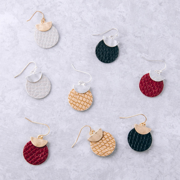 "Faux leather disc earrings featuring snakeskin details with a gold metal accent. Approximately 1"" in length."