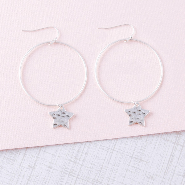 """Round metal earrings featuring star accents. Approximately 2"""" in length."""