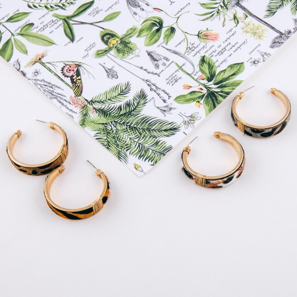"""Cowhide leopard print hoop earrings with wire wrapped details.  - Approximately 1.5"""" in diameter - Approximately 1cm in width"""